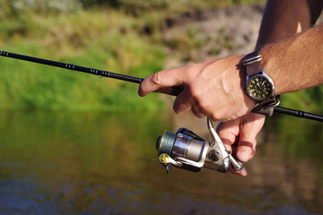 Fishing with a spinning on the river. Man catches fish, a close up of a hand and the spinning reel.