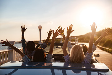 Back view of happy friends driving cabriolet with raised hands Wall mural