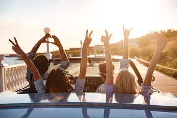 Happy friends in cabriolet with raised hands driving on sunset Wall mural
