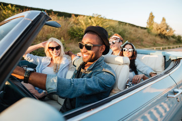Cheerful young friends driving car and smiling in summer Wall mural