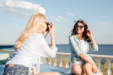 Cheerful woman sitting and posing to girl photographer in summer