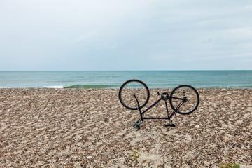 bike upside down on the beach, nobody inside