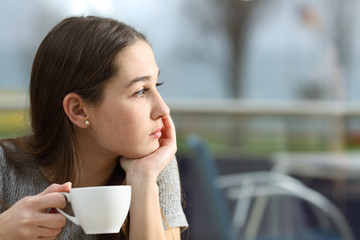 Pensive woman looking away in a coffee shop