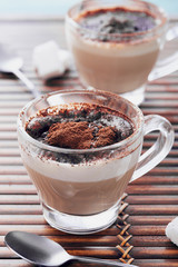 Italian cappuccino in a glass cup with cacao powder