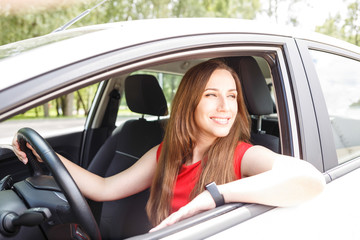 Young woman in red dress sitting in the car