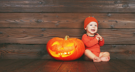 Halloween . Happy funny baby  with a pumpkin jack on a wooden