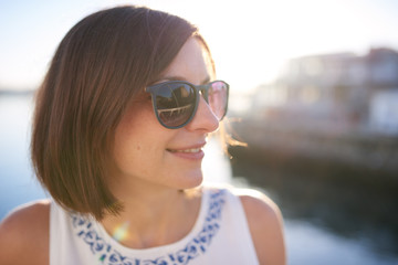 Happy caucasian woman looking off camera, wearing sunglasses and smiling with warm summer light coming through from behind her.