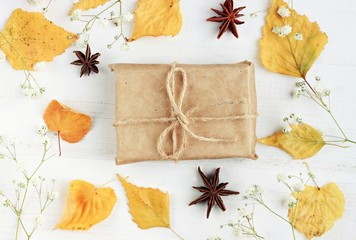 Autumn-themed handicraft gift box, decorated dried yellow leaves, flowers. Lovely fall present arrangement background.