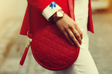Elegant outfit. Close up of red quilted leather bag handbag in hands of stylish woman. Fashionable girl on the street. Sunny day. Female fashion concept. City lifestyle. Toned