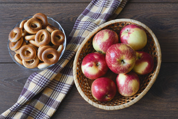 Basket with red apples, vase bagels and towel