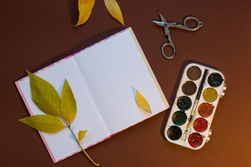 watercolor paints, scissors, yellow leaves, notebook on a brown background