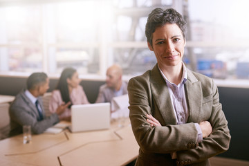 Confident businesswoman smiling at the camera while standing with her arms crossed in front of her colleagues that are seated at the table behind her.