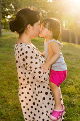 Asian Chinese Little Girls Kissing Mother at Park
