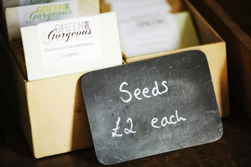 Seed packets for sale, a chalk sign with a price.