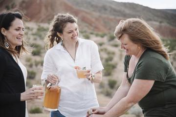 Three women standing in a desert landscape having a drink.