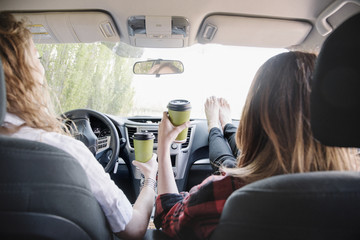 Two women in a car on a road trip, bare feet on the dashboard. View from behind.
