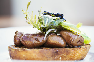 Village public house menu dish. A plate with cooked meat, sliced and arranged on a slice of bread, with vegetable garnish.