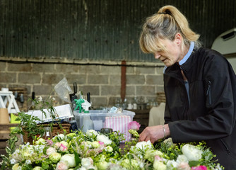 Commercial flower arranging. A woman florist working at a bench on table decorations and flower arrangements.