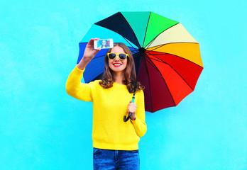 Fashion pretty smiling woman with colorful umbrella taking autum