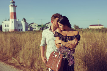 young couple hipster indie style in love walking in countryside, gentle hugs, lighthouse on background, warm summer day, sunny, bohemian outfit, vintage bag with flowers