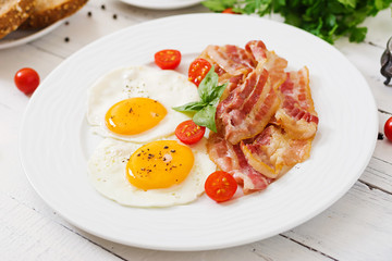 English breakfast - fried egg, tomatoes and bacon.