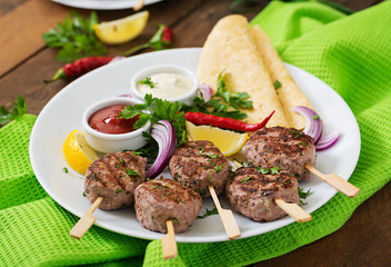 Appetizing kofta kebab (meatballs) with sauce and tortillas tacos on a white plate
