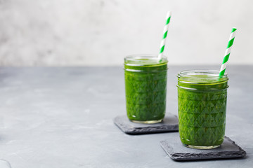 Spinach smoothie Healthy drink in glass jar on grey stone background. Copy space