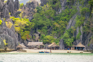 Small native village of thatched huts on the coast of Coron Island