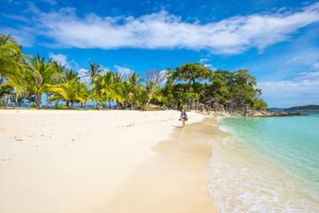 A lady walking on the white sandy beach