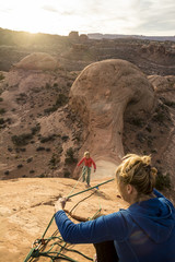 A woman lowering a young girl down sandstone prow, Kane Creek Road, Moab, Utah.