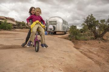 Two girls playing on a tiny mountain bike on desert sandstone, Moab, Utah.