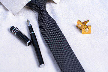 Business accessories (cufflinks, fountain pen) in the men's classic white shirt with tie