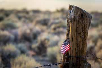US Flag stuck in log fence post