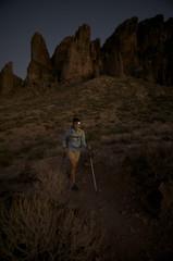 Woman hikes at night by headlamp on the Treasure Loop Trail in Lost Dutchman State Park near Phoenix, Arizona November 2011.