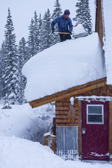 A man shovelling snow off hut roof on Molas Pass near Silverton, Colorado.