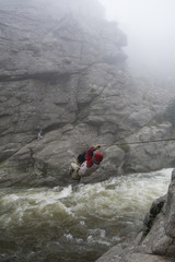 A climber crosses a swollen creek on a tyrolean traverse.