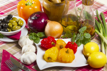 Pickled peppers, red and yellow, five pieces on a white plate next to olives, olive oil, lemon, onion and garlic.
