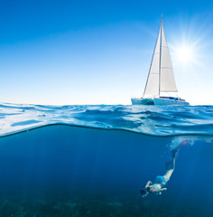 Young woman snorkeling under the boat
