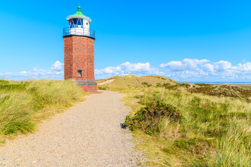 Fototapete - Lighthouse on sand dune against blue sky with white clouds on northern coast of Sylt island near Kampen village, Germany