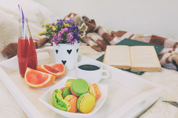 Breakfast in bed with hot coffee and macaroons. Healthy breakfast kept on bed with books and flowers Close up of a cup of coffee with cookies, fresh juice and grapefruit on wooden tray in bed. Toned