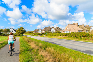 Young woman tourist rinding a bike along a road in Keitum village with typical straw roof houses on Sylt island, Germany