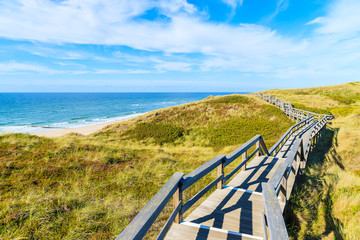 Fototapete - Wooden walkway along a coast of North Sea and view of beautiful beach near Wenningstedt village, Sylt island, Germany