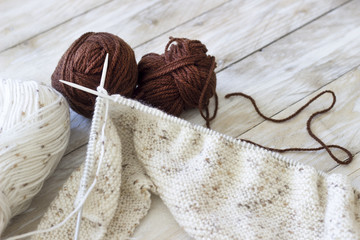 Skeins of wool and knitting needles on wooden background