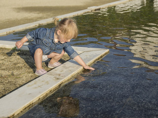 little girl touches the water of a pond