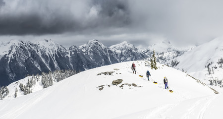 A group of climbers drag sleds of gear over the snow in the Mount Baker Backcountry.