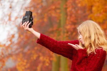 Woman with old vintage camera taking selfie photo.