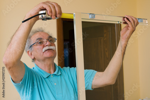 Senior man installing and measuring a shower box do it yourself senior man installing and measuring a shower box do it yourself concept solutioingenieria Gallery