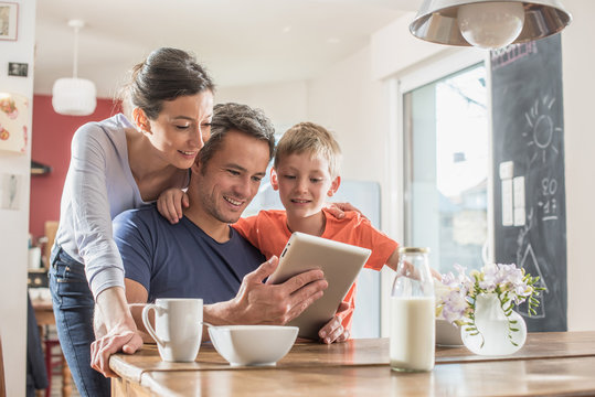 A family using a tablet while having breakfast in the kitchen