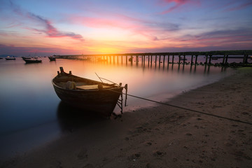 Small fishing boats moored beached on the beach during time the sunset and the beautiful natural of the colorful sky at Bang Phra beach , Chonburi province in Thailand