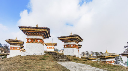 Fototapete - Dochula pass 108 chortens (Asian stupas) is the memorial in honour of the Bhutanese soldiers in the Timpu city with the grass landscape and cloudy sky background, Bhutan